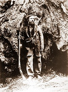 A man with beard and long hair is holding a long gun and is standing in front of a very large tree.