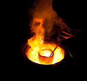 English: Melting metal in a ladle for casting ...