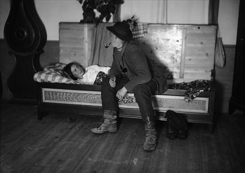 Nattfrieri. En man sitter på sängkanten och pratar med liggande kvinna. Värmland, Mangskogs socken. (public domain)
