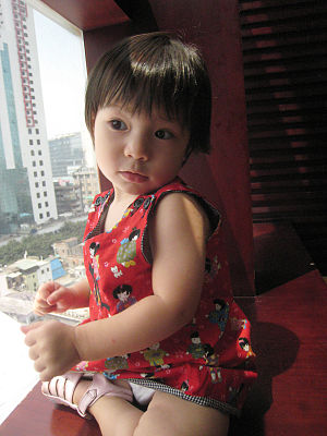 A little Chinese girl by a window.