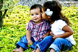 English: Brother and sister sitting in flowers