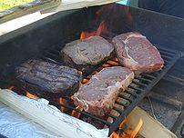 Beef steaks over wood.