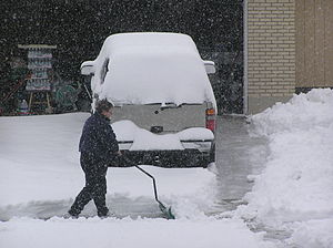 English: Neighbor shoveling snow from their dr...