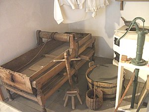 An exhibit of old laundry equipment arranged i...