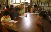 Volunteer reading to kids in the library room