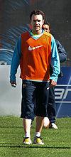 Un homme portant un long short bleu foncé et un sweat bleu clair sous un bavoir orange.