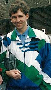 Un homme souriant aux cheveux noirs porte un haut de survêtement blanc, vert et bleu par-dessus une chemise bleue. Il tient un sac de toilette sous son bras droit.