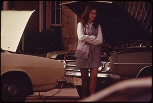 COMMUTER WAITS AS HER CAR BATTERY IS CHARGED. ...
