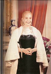 A picture of a Evita, former first lady of Argentina. Her hair is drawn into a tight bun at the back. She is wearing a black, low-cut dress. Around her neck is a number of chains. The lady's hands are folded in her front and she has a white fur shawl around her. This is an official state portrait taken in the Argentine government house, the Casa Rosada.