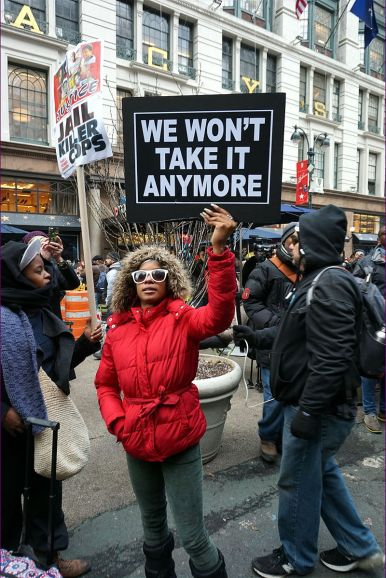 "Photo of a black woman holding a sign that says, ""We won't take it anymore."""