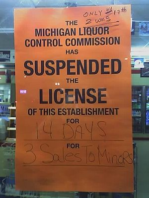A sign posted on the door of a convenience sto...