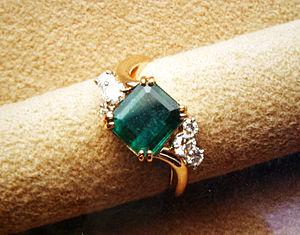 A faceted emerald cut emerald mounted in a com...