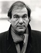 A man, wearing a coat and scarf, furrows his brow.