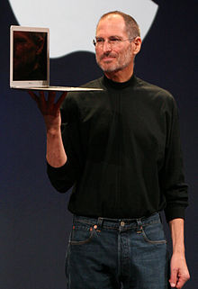 Crotch-high portrait of man in his fifties wearing blue jeans and a black turtleneck shirt, carrying an open laptop computer in his right hand, large Apple logo cut off behind him