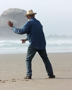 An elderly man performing tai chi in front of ...