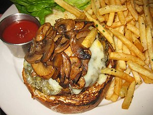 English: Veggie burger with fried mushrooms.
