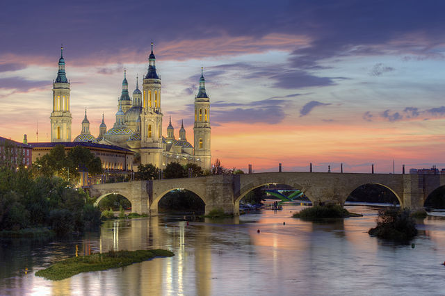 https://i1.wp.com/upload.wikimedia.org/wikipedia/commons/thumb/5/57/Basilica_of_Our_Lady_of_the_Pillar_and_the_Ebro_River%2C_Zaragoza.jpg/640px-Basilica_of_Our_Lady_of_the_Pillar_and_the_Ebro_River%2C_Zaragoza.jpg