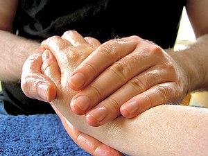 Photograph of a man massaging a woman's hand w...