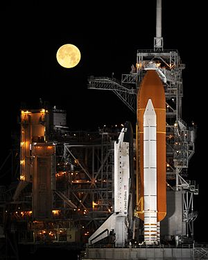 A nearly full moon sets as the space shuttle D...