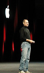 Full-length portrait of man about fifty wearing jeans and a black turtleneck shirt, standing in front of a dark curtain with a white Apple logo
