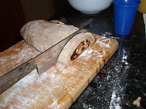A 'loaf' of raw cinnamon roll dough being cut ...