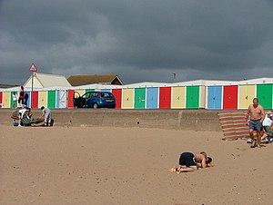 English: Colourful beach huts against a black sky