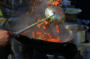 Stir frying (爆 bào) in the wok