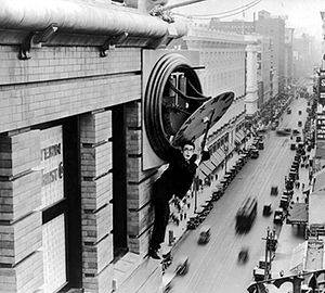 Actor and comedian Harold Lloyd hangs from a p...