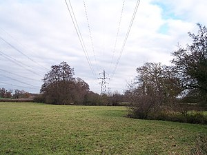 English: Powerlines. Looking east across the s...