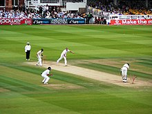 Men in cricket whites play upon a green grass cricket field amidst a stadium.