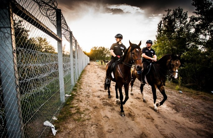 Mounted policemen at Hungary-Serbia border barrier