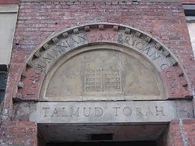 "Stones over a doorway arch with the incomplete name ""Roumanian-American Cong"" in carved capital letters. Beneath, carved into the lintel, are the words ""Talmud Torah"", also in capital letters. The two surround a carving of two tablets with Hebrew writing, representing the Ten Commandments."