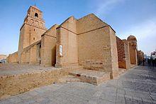Vue extérieure de la mosquée, centrée sur l'angle nord-ouest, montrant plusieurs contreforts de l'enceinte et le minaret. Les contreforts, de diverses formes et dimensions, sont pour la plupart épais et saillants.