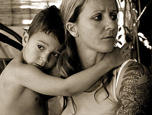 Mother with tatooed arm and wet child.