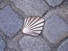 photographie d'une coquille Saint-Jacques en cuivre insérée dans les pavés d'une rue de Limoges et marquant le passage de la Via Lemovicensis menant à Saint-Jacques de Compostelle