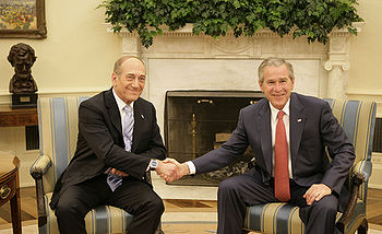 President George W. Bush exchanges handshakes ...