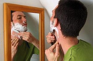 A man shaving with a cut-throat razor