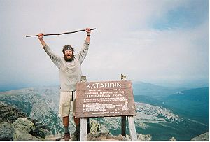 A thru-hiker celebrates the successful complet...