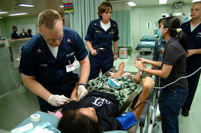 US Navy 050406-N-0357S-008 Hospital Corpsman 2nd Class Jason Moore prepares to put an IV in the arm of an Indonesian women suffering from an ankle injury