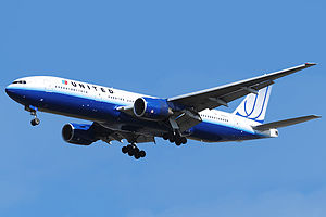 Aircraft landing approach. Front quarter view of twin-engine jet in flight with flaps and landing gear extended.