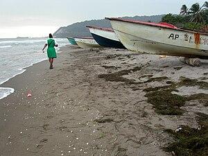 A schoolchild walks past a row of fishing boat...