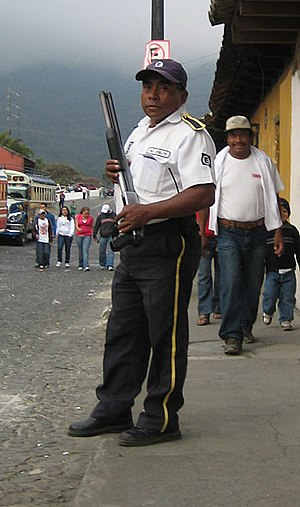 English: Private security guard with shotgun, ...