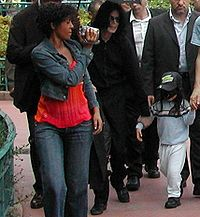Sekelompok orang dewasa dan anak diperlihatkan  dalam foto.  Seorang wanita Amerika Afrika dengan cokelat pendek yang  mengenakan  jaket jean dan sepasang lampu mencuci jeans dengan kemeja  merah  terlihat memegang kamera video, yang menunjuk ke depan. Di sebelah  kiri  wanita ada payung hitam terbuka yang diselenggarakan di atas  laki-laki  kulit putih dengan rambut hitam panjang yang mengenakan  pakaian hitam  semua. Di depan ada laki-laki adalah anak dengan rambut  hitam yang  mengenakan topi hitam dengan kemeja biru, celana putih dan  sepatu  hitam. Untuk yang paling jauh meninggalkan makan ada dua pria  berkulit  putih dengan rambut coklat gelap. Di latar belakang,  pohon-pohon,  semak-semak dan orang dapat dilihat.