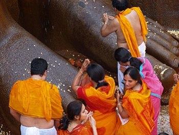 English: Jains praying at the feet of Lord Bah...
