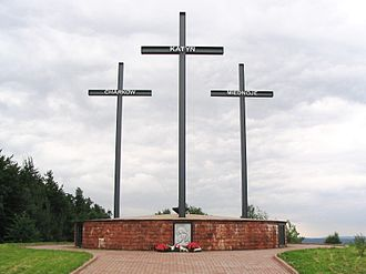 La photographie couleur représente une allée dallée qui conduit à une surélévation maçonnée supportant trois croix métalliques. Chacune porte le nom des massacres subis par les Polonais: Katyn, Charkow et Miednoje. Devant le mémorial, un bas relief est fleuri par trois gerbes de fleurs rouges et noires.