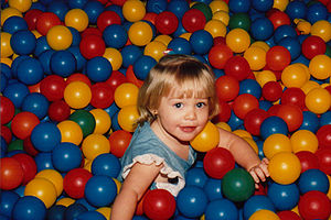 A toddler in a ball pit.