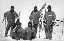 Five men(three standing, two sitting on the icy ground) in heavy polar clothing. All look exhausted and unhappy. The standing men are carrying flagstaffs and a Union flag flies from a mast in the background. Scott's party at the South Pole. Left to right: Wilson; Bowers; Evans; Scott; Oates
