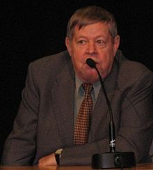 Color photo: Medium shot of Arto Paasilinna, sitting behind a table, speaking in a microphone.