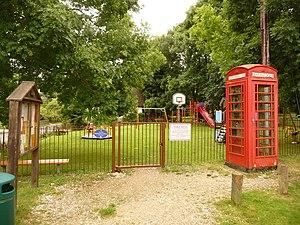 English: Farnham: phone box and playground Use...