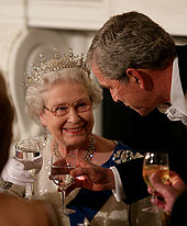 In evening wear, Elizabeth and President Bush hold wine glasses of water and smile